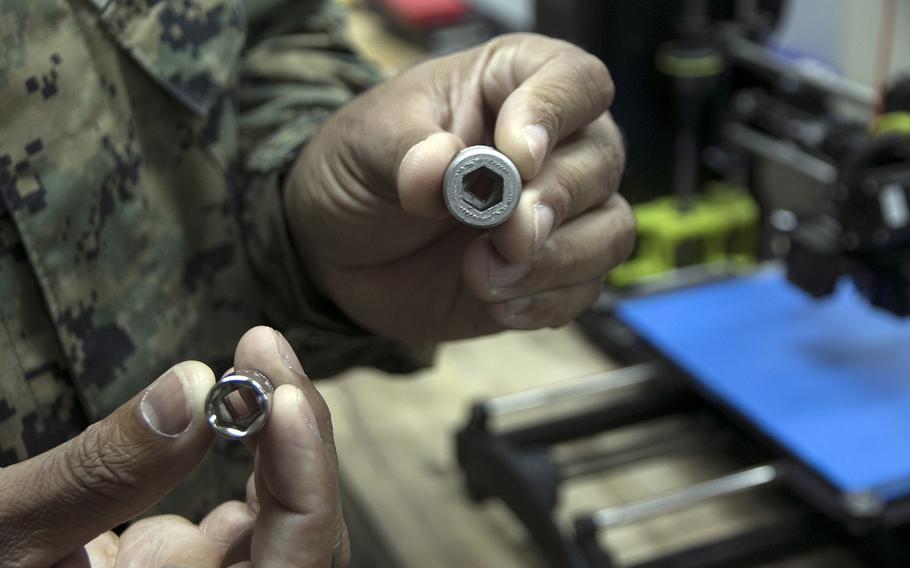 Marine Staff Sgt. Quincy Reynolds of the III Marine Expeditionary Force's 3rd Maintenance Battalion holds two sockets inside his shop at Camp Kinser, Okinawa, Jan. 16, 2020. The one on the right was made with the unit's new Markforged Metal X 3D printer.