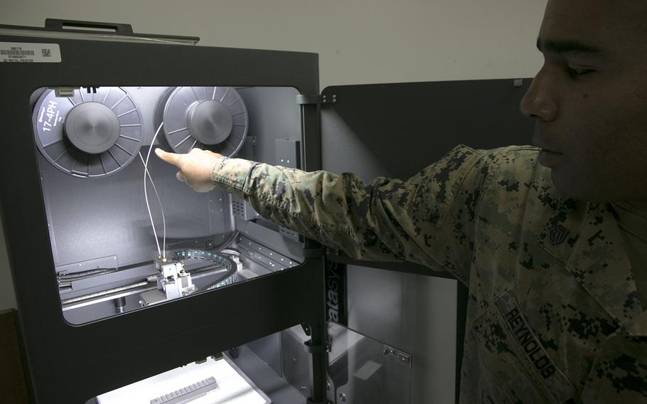 Marine Staff Sgt. Quincy Reynolds of the III Marine Expeditionary Force's 3rd Maintenance Battalion shows off the unit's new Markforged Metal X 3D printer at Camp Kinser, Okinawa, Jan. 16, 2020.