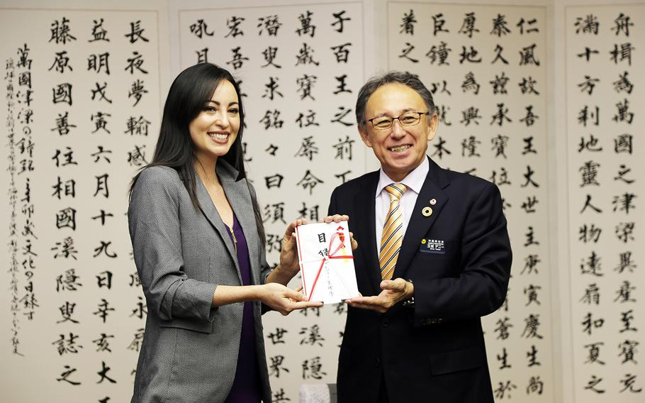 Marine Corps spouse Mari Gregory presents Okinawa Gov. Denny Tamaki with more than $11,000 in donations for the restoration of Shuri Castle, Thursday, Feb. 6, 2020. The popular cultural landmark was devastated by fire in October.