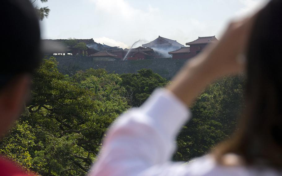 People watch as firefighters work a blaze at Shuri Castle in Naha, Okinawa, Oct. 31, 2019.