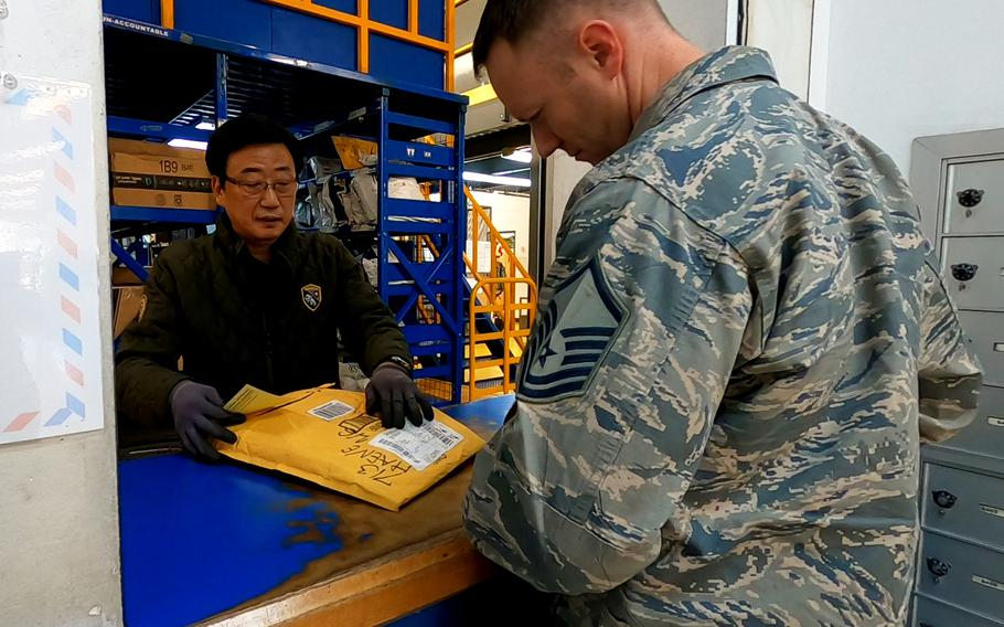 A South Korean man working for U.S. Forces Korea assists a service member at the post office on Osan Air Base, South Korea, Thursday, Feb. 6, 2020.