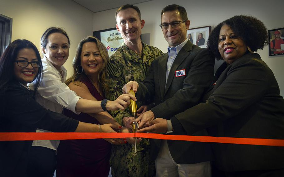 The USO Yokosuka team helps base commander Capt. Richard Jarrett and USO Pacific Region Vice President Charles Hyde cut the ribbon to reopen the renovated facility at Yokosuka Naval Base, Japan, Friday, Feb. 7, 2020.