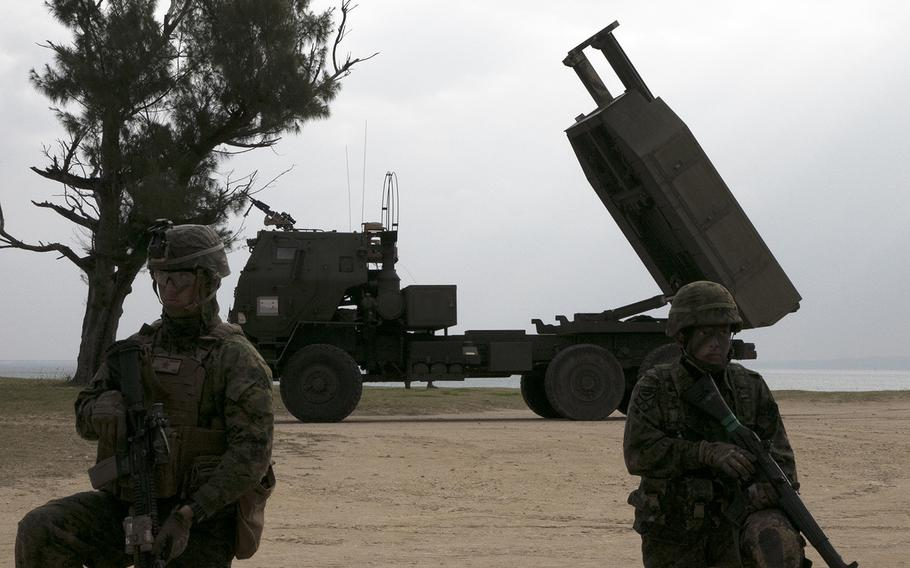 A U.S. Marine, left, and a Japan Ground Self-Defense Force soldier guard an M142 High Mobility Artillery Rocket System during an exercise in Kin, Okinawa, Sunday, Feb. 9, 2020.