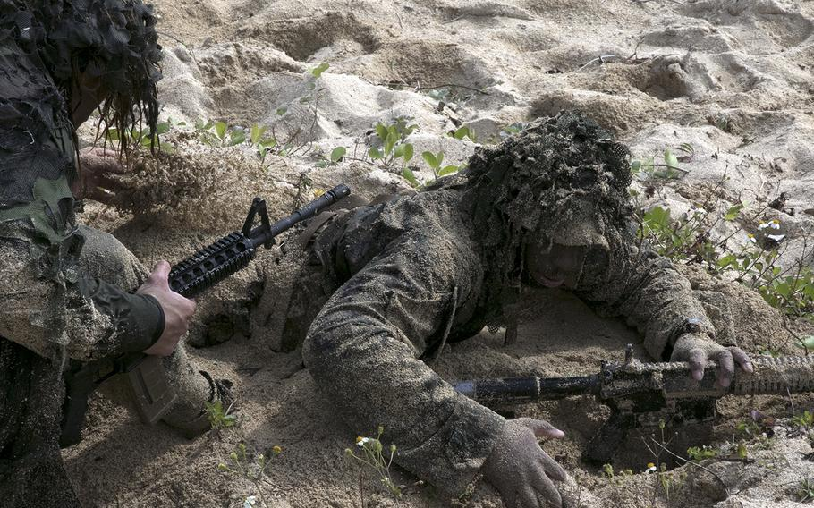 A member of the 31st Marine Expeditionary Unit is camouflaged with sand during an amphibious exercise on Kin, Okinawa, Sunday, Feb. 9, 2020.