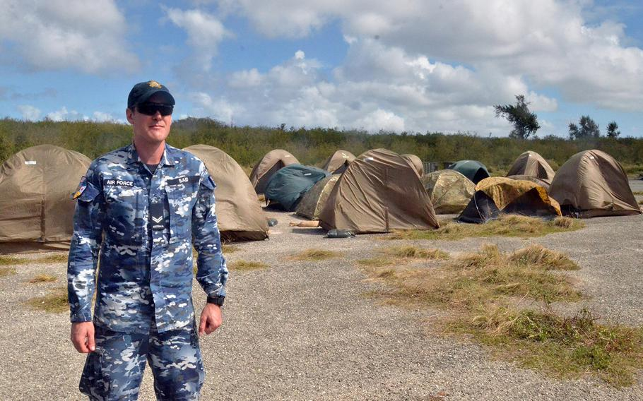 An Australian service member stands near a wind-battered encampment during Cope North disaster response and humanitarian assistance training on the island of Tinian, Tuesday, Feb. 18, 2020.