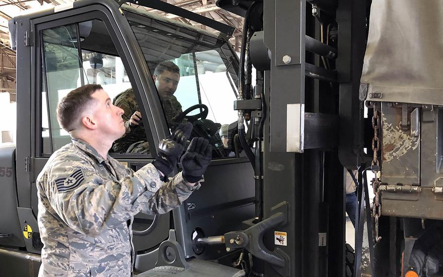 Air Force Tech. Sgt. Daniel Blair guides Staff Sgt. William McAtee as he unloads Meals, Ready to Eat from a Japan Ground Self-Defense Force truck at Yokota Air Base, Japan, Friday, Feb. 21, 2020.