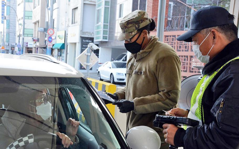 Pvt. Daija Gillam, 22, of the 25th Transportation Battalion, screens drivers before allowing them to enter Camp Walker in the coronavirus-hit city of Daegu, South Korea, Saturday, Feb. 22, 2020.