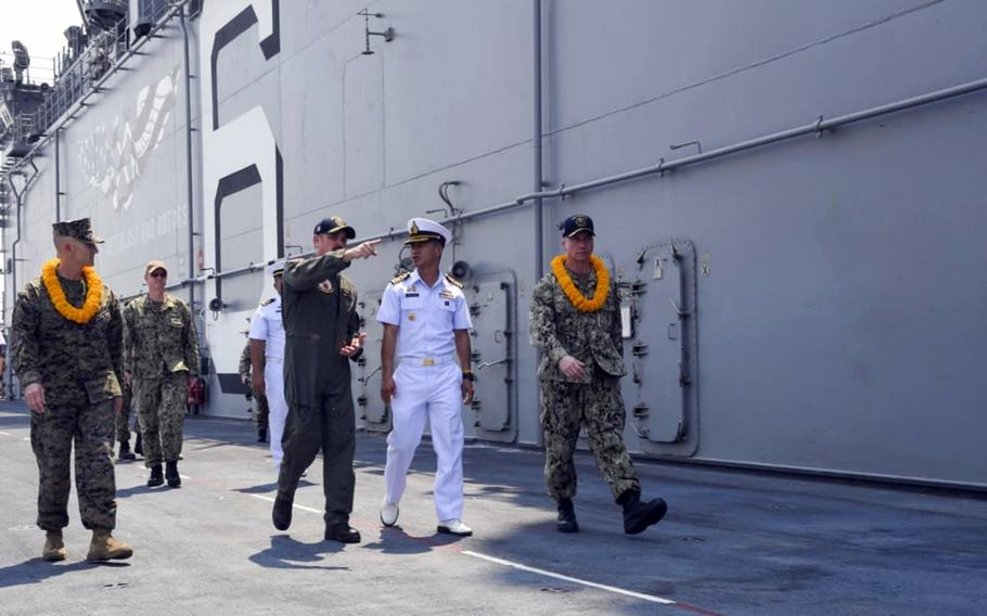 U.S. Navy Cmdr. Stephen Audelo, pointing, guides Royal Thai Navy Capt. Arpa Chapanon during a tour of the amphibious assault ship USS America in Laem Chabang, Thailand, Feb. 22, 2020.