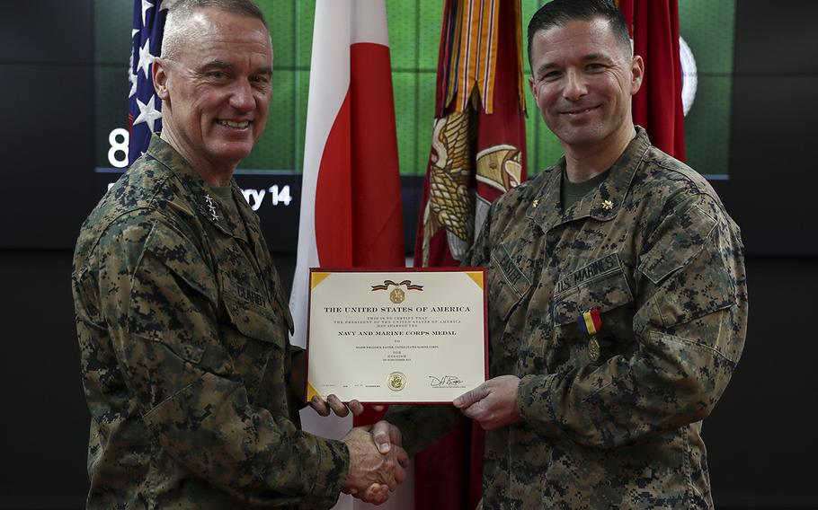 Marine Maj. William Easter, right, receives the Navy and Marine Corps Medal from III Marine Expeditionary Force commander Lt. Gen. H. Stacy Clardy at Camp Courtney, Okinawa, Feb. 14, 2020.