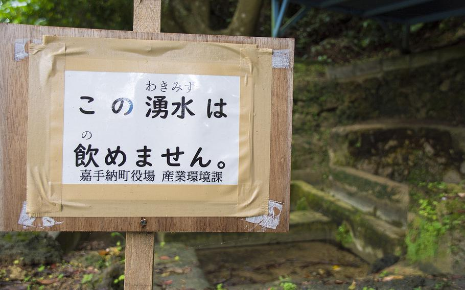 A sign posted by town officials to warn people not to drink nearby polluted spring water is pictured in Kadena, Okinawa, May 10, 2019.