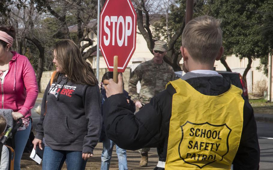 A crossing guard stops traffic for students near Joan K. Mendel Elementary School at Yokota Air Base, Japan, Friday, Feb. 28, 2020.