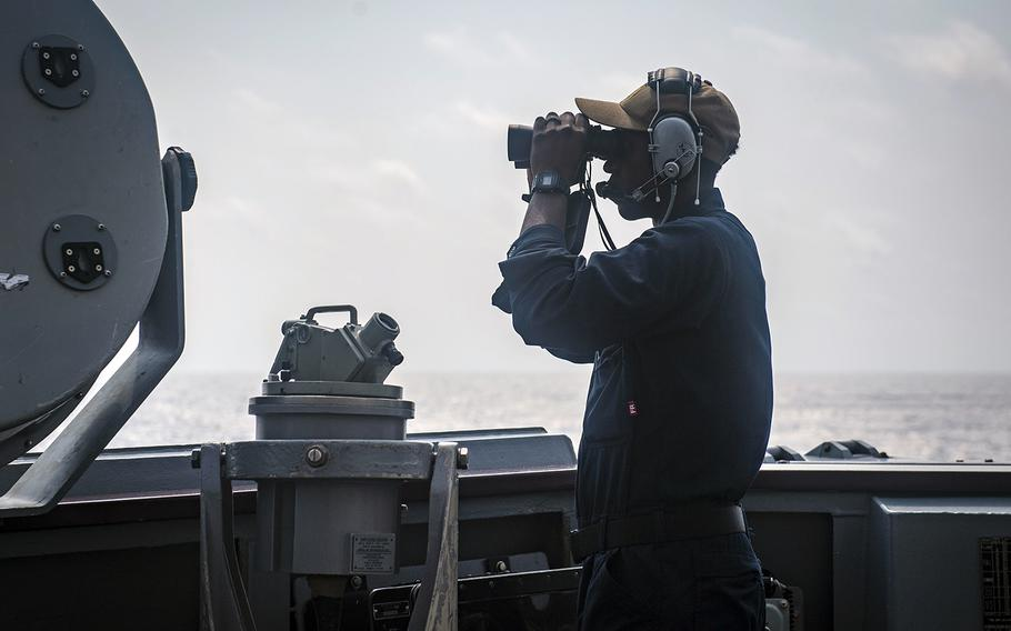 Airman Beniaah Norris scans the horizon while standing watch aboard the guided-missile destroyer USS McCampbell in the South China Sea, March 10, 2020.