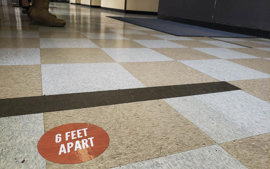 A floor decal inside the post office at Yokota Air Base in western Tokyo encourages social distancing, Friday, March 27, 2020.