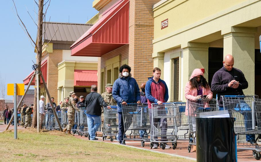 Customers wait in line to enter the commissary at Camp Humphreys, South Korea, Friday, March 27, 2020.