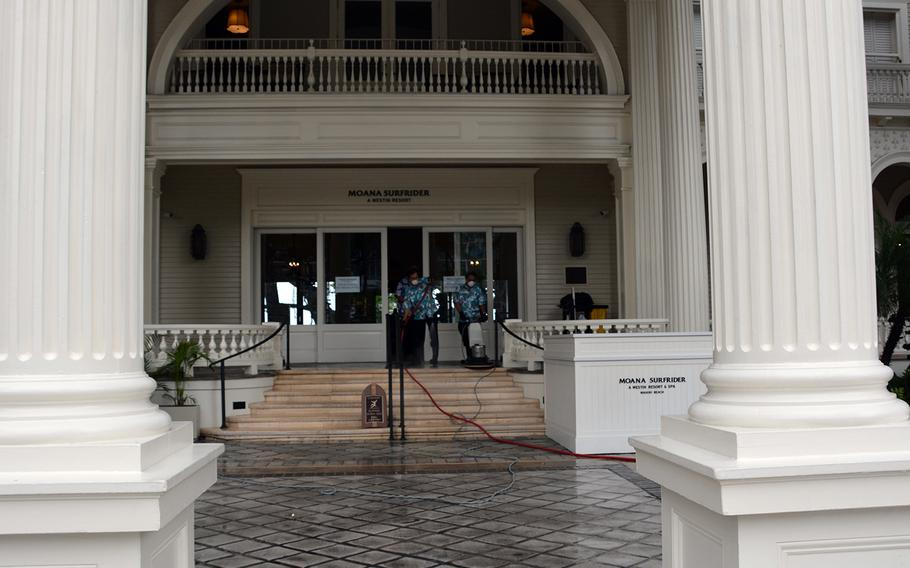 Wearing protective masks, employees on March 31, 2020, clean and disinfect the main entrance of Moana Surfrider hotel, which like most hotels on Waikiki Beach has suspended operations in the wake of state and city shelter-in-place orders.