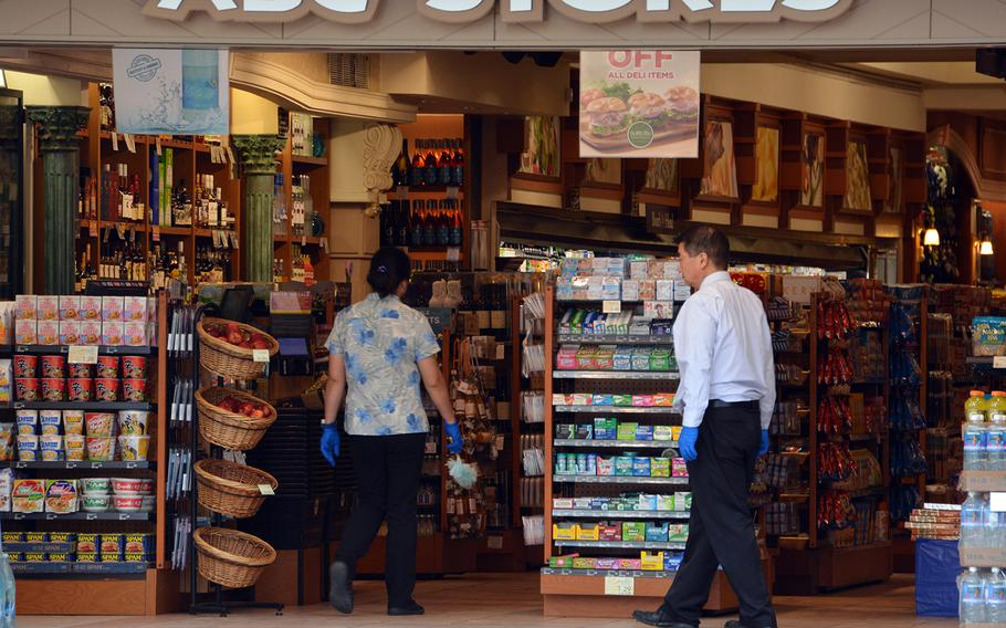 Workers at an ABC Store on Kalakaua Avenue, Waikiki Beach in Hawaii, clean and disinfect in the absence of customers, March 31, 2020.