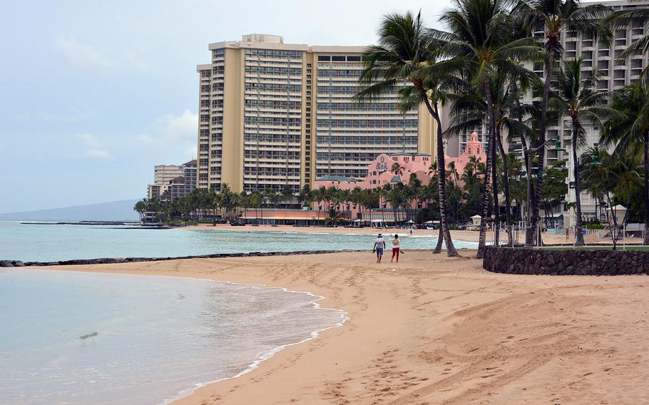 Two strollers have the Waikiki Beach seaside all to themselves, March 31, 2020.