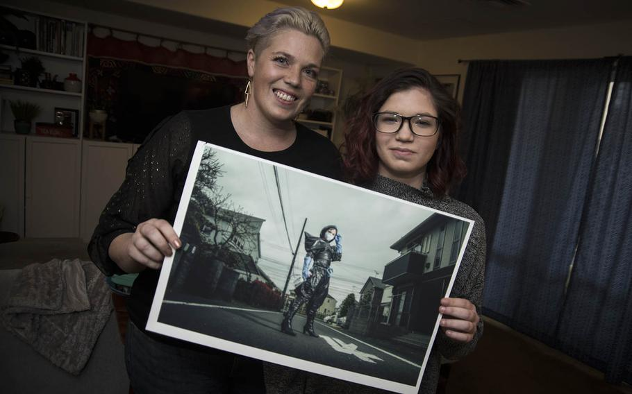 Cari Payer and her daughter, Sage, pose with an image from their coronavirus photo project inside their home at Yokota Air Base, Japan, Wednesday, April 1, 2020.