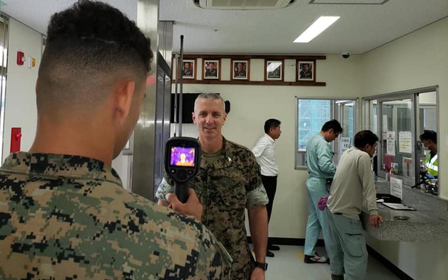 Col. Vincent Ciuccoli, commander of Headquarters and Support Battalion at Camp Smedley D. Butler, is screened for coronavirus symptoms at Camp Schwab, Okinawa, March 30, 2020.