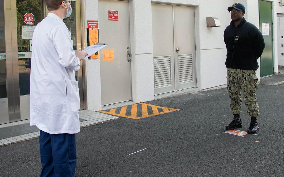Hospital corpsman Nicholas Bond, left, questions fellow Petty Officer 3rd Class Darien Huggins outside the health clinic at Sasebo Naval Base, Japan, April 2, 2020.