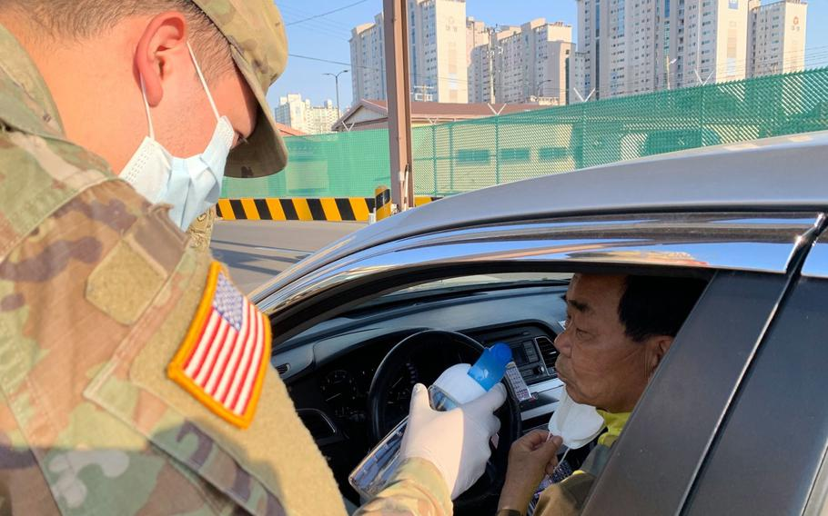 A driver takes a smell test as part of coronavirus screening measures at Camp Henry, South Korea, Friday, April 3, 2020.
