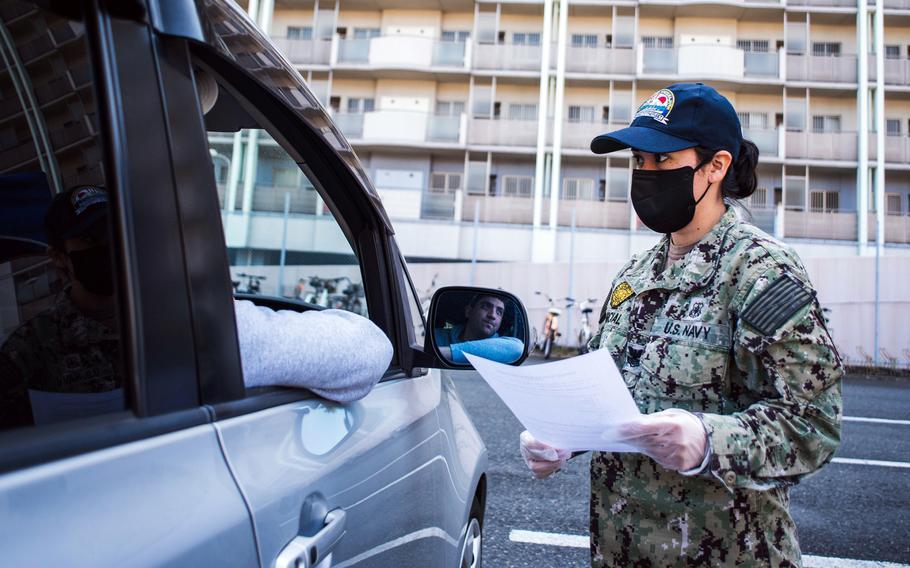 A sailor practices screening drivers for coronavirus symptoms at Yokosuka Naval Base, Japan, March 18, 2020.
