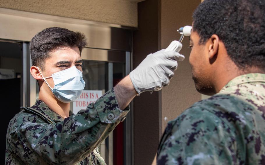 A hospital corpsman checks the temperature of a sailor visiting a health clinic at Naval Air Facility Atsugi, March 26, 2020.