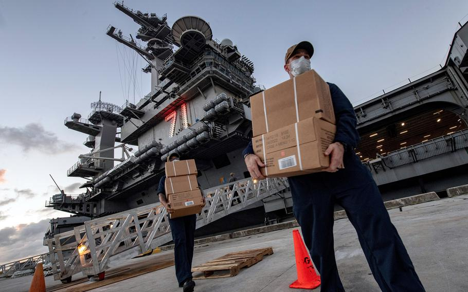 Sailors assigned to the aircraft carrier USS Theodore Roosevelt move meals, ready to eat for shipmates who have tested negative for the coronavirus at Naval Base, Guam, April 7, 2020.