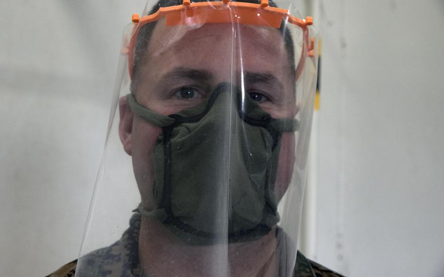 Chief Warrant Officer 4 Sean Flores of the III Marine Expeditionary shows off face mask and face shield frames that were 3D printed at Camp Kinser, Okinawa, Wednesday, April 8, 2020.