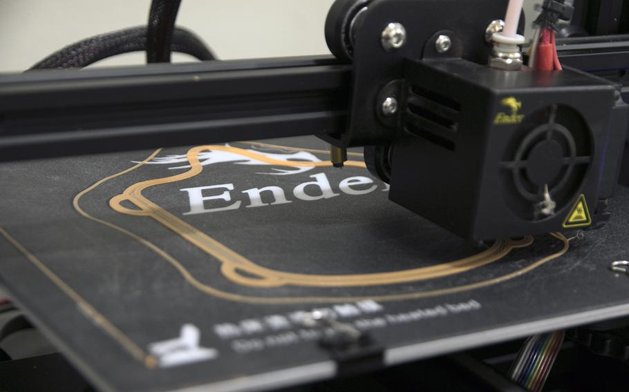 A Creality Ender 3 Pro 3D printer makes a face mask frame at the 3rd Maintenance Battalion's Camp Kinser warehouse, Wednesday, April 8, 2020.