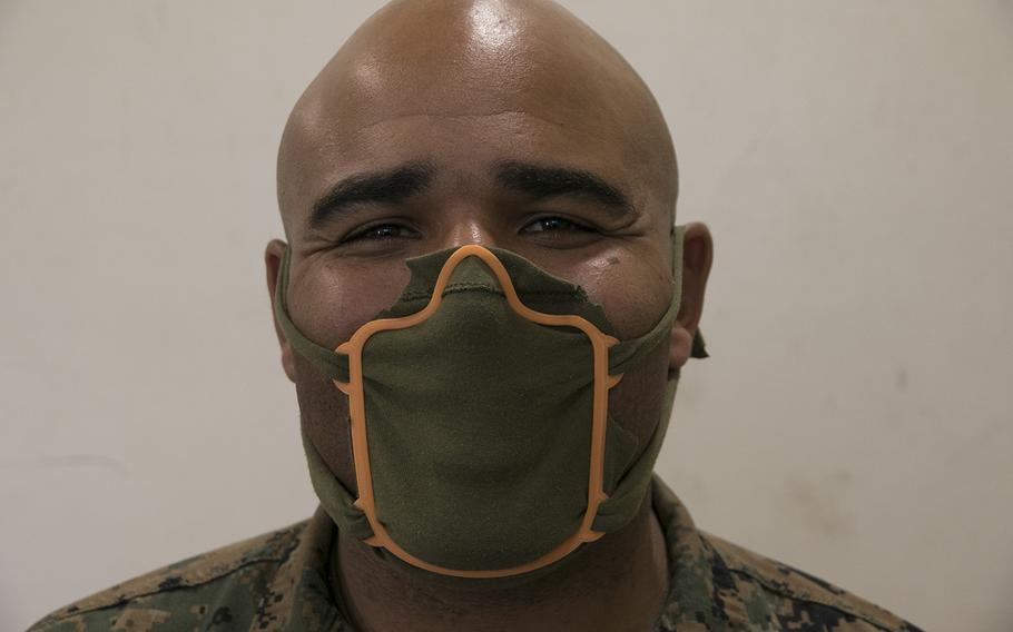 Marine Staff Sgt. Quincy Reynolds of the III Marine Expeditionary Force's 3rd Maintenance Battalion shows off his 3D printed face mask frame at Camp Kinser, Okinawa, Wednesday, April 8, 2020.
