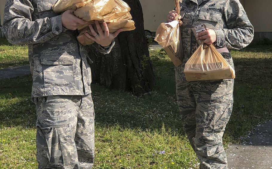 Air Force Capt. Lance Brown, a chaplain, and Airman 1st Class Stefanie Davidson, a chaplain's assistant, deliver worship materials to families coping with the coronavirus pandemic at Yokota Air Base, Japan.