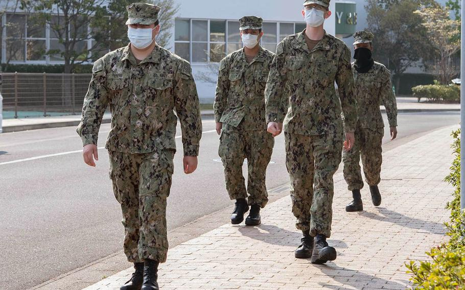 Sailors assigned to Sasebo Naval Base, Japan, wear face masks and practice social distancing while walking on base April 9, 2020.