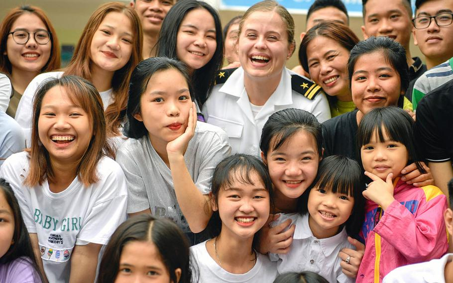 A Navy public affairs officer poses for a photo with children at the Dorothea's Project Legacies Charity Center, Danang, Vietnam, during the USS Theodore Roosevelt's port call March 6, 2020.