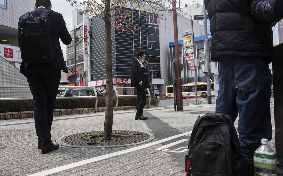 Smokers practice social distancing at a smoking area outside the main train station in Fussa, Japan, Friday, April 17, 2020.