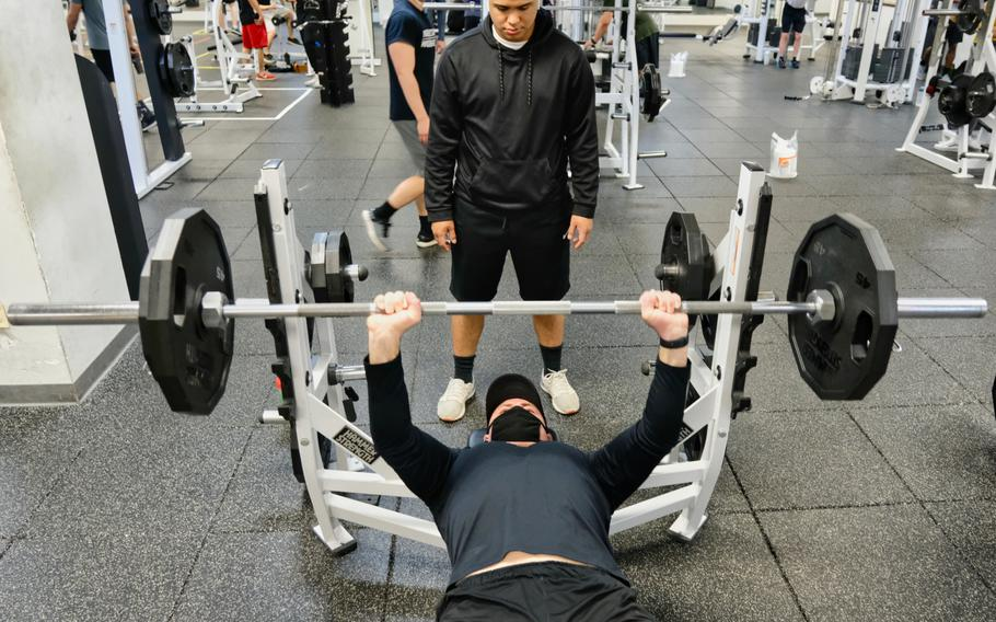 Staff Sgt. Elvis York lifts weights wearing a mask while his spotter maintains proper social distance inside Collier Community Fitness Center at Camp Humphreys, South Korea, Saturday, April 18, 2020.
