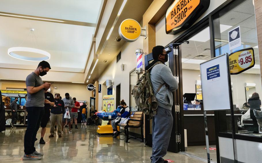 Customers practice social distancing while waiting to enter a barbershop at Camp Humphreys, South Korea, Saturday, April 18, 2020.