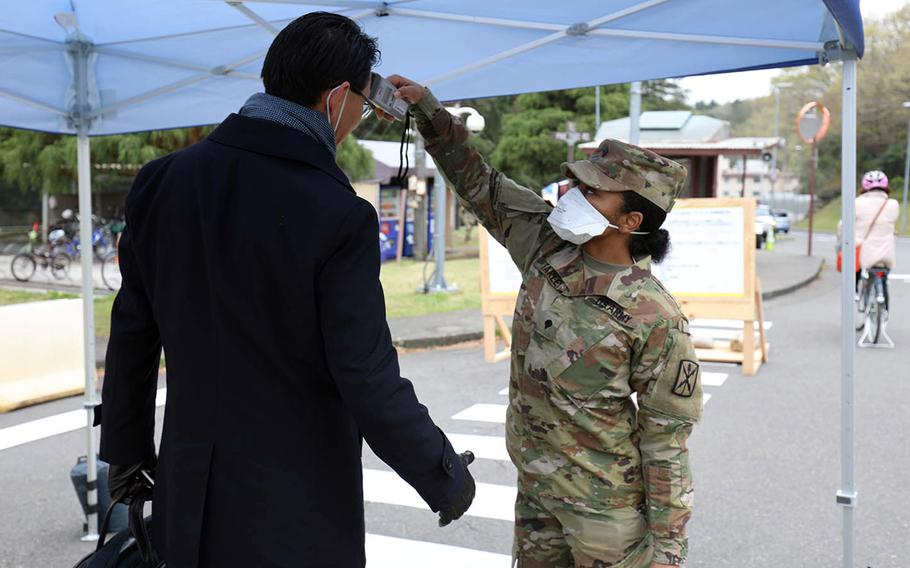 Spc. Brittany Farley takes the temperature of a man entering Camp Zama, Japan, March 31, 2020.
