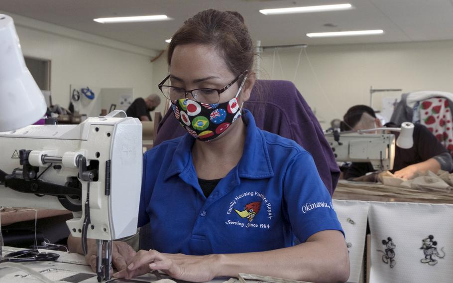 Nami Takaki, of the 718th Civil Engineer Squadron furniture repair shop, makes face masks out of dust-cover fabric at a warehouse outside Camp Shields, Okinawa, Monday, April 20, 2020.