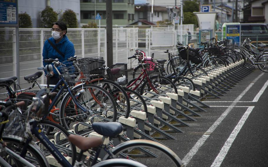 A man parks his bicycle near the main train station in Fussa, Japan, Thursday, April 23, 2020. Fussa borders Yokota Air Base, home of U.S. Forces Japan, 5th Air Force and the 374th Airlift Wing.