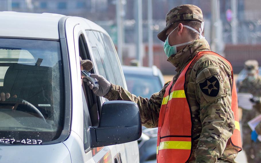 A motorist is screened for the coronavirus before entering Camp Humphreys, South Korea, Feb. 27, 2020.