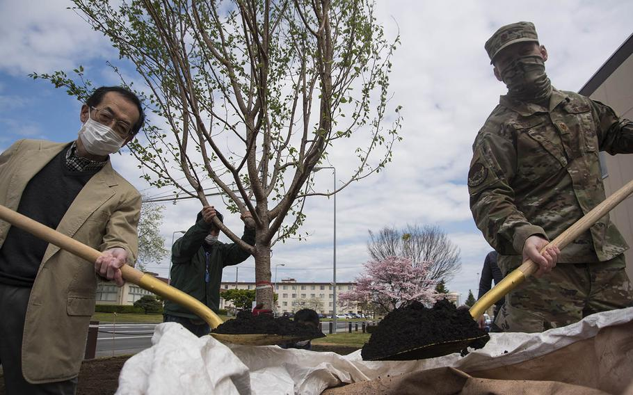 Yoshitaka Yamaguchi, left, the 374th Civil Engineer Squadron's cultural resource manager, and Maj. Trent Bolte, the squadron's operations flight commander, pose while planting a cherry tree at Yokota Air Base, Japan, Friday, April 24, 2020.