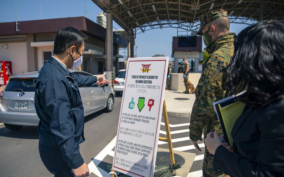 Col. Lance Lewis, commander of Marine Corps Air Station Iwakuni in Japan, shows Iwakuni city Mayor Yoshihiko Fukuda the precautionary measures in place at the base to prevent the spread of the coronavirus, April 14, 2020.