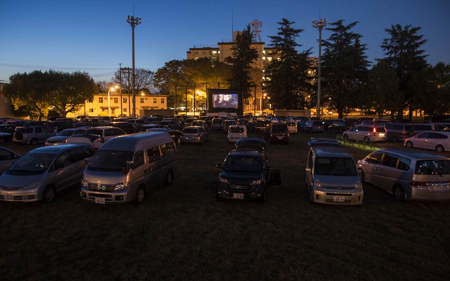 Families gather to watch a free drive-in movie on a sports field at Yokota Air Base, Japan, Saturday, April 25, 2020.
