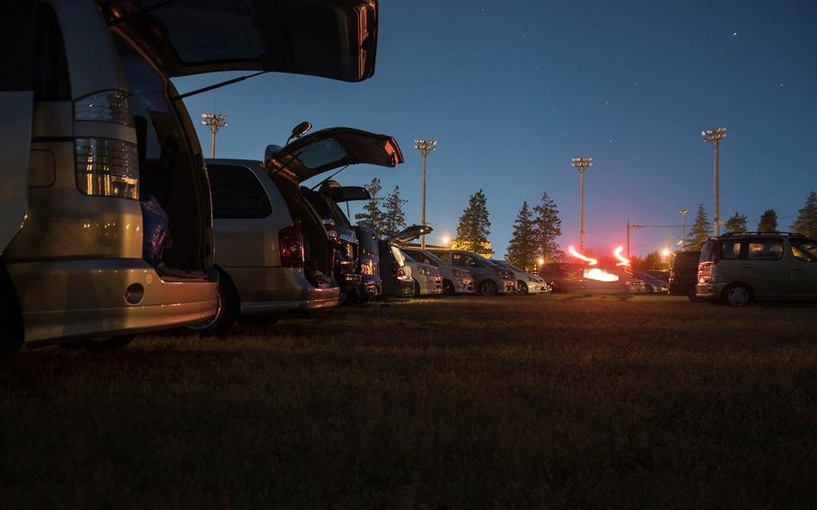 Vehicles line up on a sports field for a drive-in movie at Yokota Air Base, Japan, Saturday, April 25, 2020.