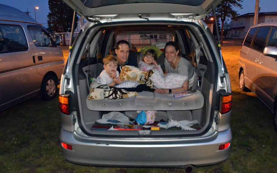 Air Force Col. Doyle Pompa of Albuquerque, N.M., prepares to watch a drive-in movie with his wife, Gina, daughter Helena and son Rocco at Yokota Air Base, Japan, Saturday, April 25, 2020.