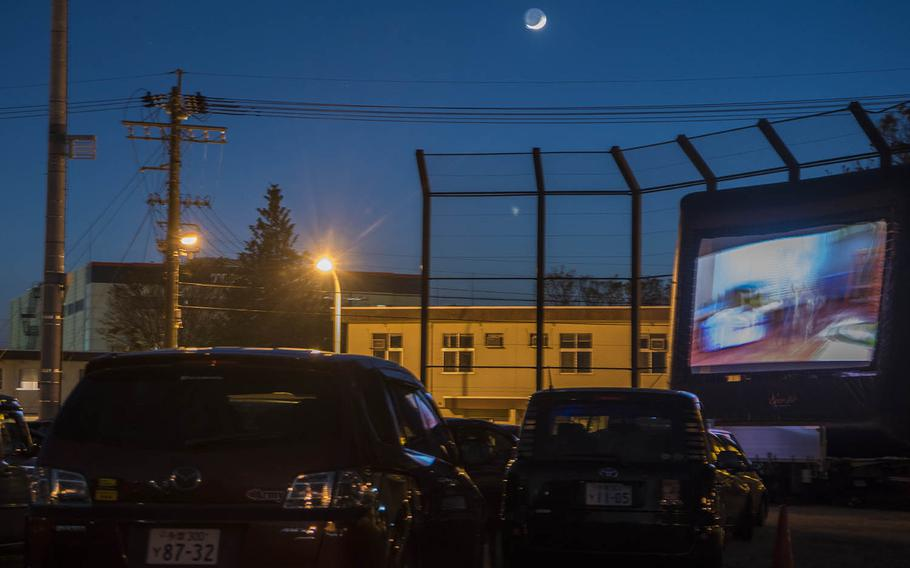 """Families in cars watch a free showing of """"Toy Story 4"""" on an inflatable outdoor screen at Yokota Air Base, Japan, Saturday, April 25, 2020."""