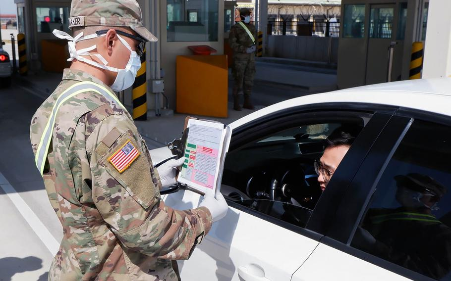 A soldier with the 2nd Armored Brigade Combat Team, of Fort Riley, Kan., interviews someone coming through the Adams Gate at Camp Humphreys, South Korea, for indicators of coronavirus on April 7, 2020.