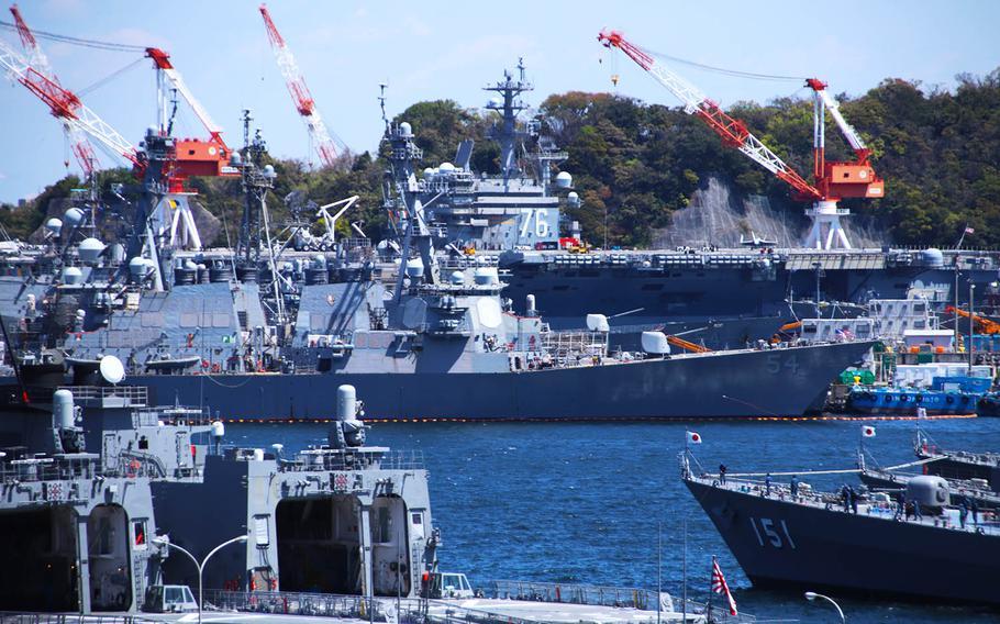 The aircraft carrier USS Ronald Reagan stands above other Navy and Japan Maritime Self-Defense Force ships at Yokosuka Naval Base, Japan, April 14, 2020.