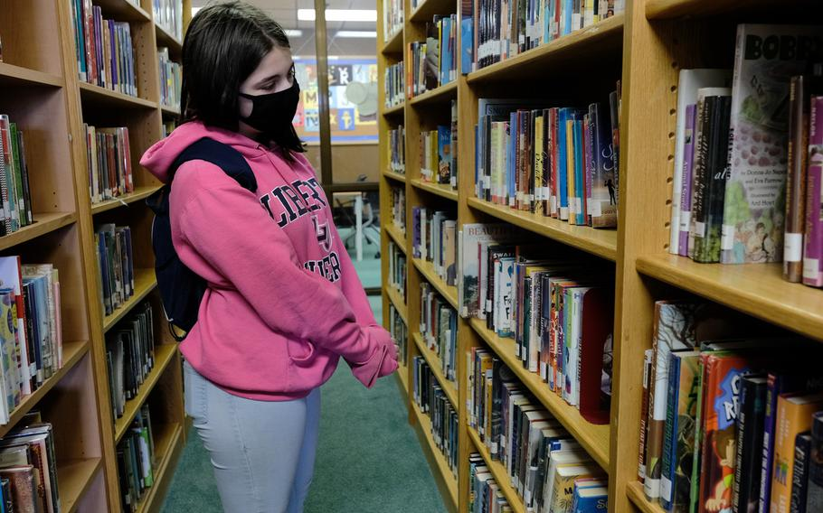 Osan Middle High School seventh-grader Charis Henry searches for a book at the Osan Air Base library in South Korea, Wednesday, April 29, 2020.